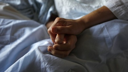 A woman holds the hand of her mother who is dying from cancer during her final hours at a palliative care hospital in Winnipeg