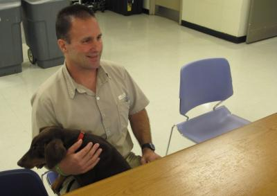 Inmate Scott Abram, holding a training dog, Ziva,  talks about his work counseling fellow inmates including some who are dying and spending their last days in a prison hospice program, on Friday, Sept. 11, 2015 in Columbus, Ohio. Abram, serving 15 years to life for murder, also trains puppies that may end up as pilot dogs.  (AP Photo/Andrew Welsh-Huggins)