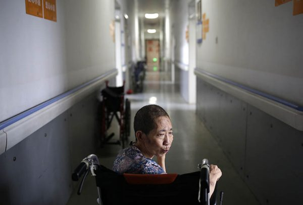 A woman sits in a wheelchair in the hallway of Songtang Hospice, Beijing, July 19, 2016.