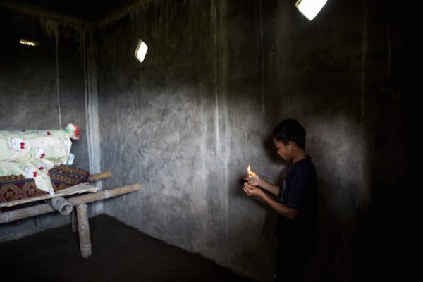 A boy lights incense in front of Lucas Payung's body before the Ma'Nene ritual in Barrupu Village, Toraja, South Sulawesi.