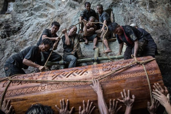 "People lift the coffin of Liling Saalino to a stone grave, or Liang, during a burial ritual, or Rambu Solo ceremony, in Lemo village, Toraja, South Sulawesi, Indonesia. During the procession, people chat ""Tau Tae Sengke,"" which means nobody should be angry."