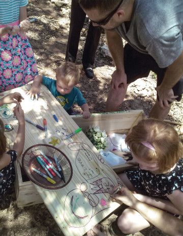 L.J.'s family decorates his casket in preparation for burial.