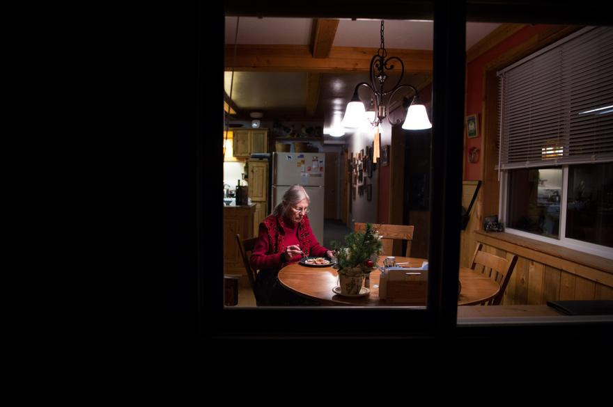 """Jane Faller eats dinner by herself as snow settles outside her home in Republic, Wash., on Tuesday. Her children worry about her making it through the winter, but her friends Steve and Deb Anthes regularly check in on her, and a neighbor plows her driveway. Still, the solitude can be unrelenting. """"It's an empty home,"""" she said."""