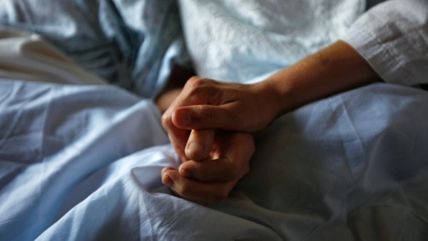 A woman holds the hand of her mother who is dying from cancer during her final hours at a palliative care hospital in Winnipeg in 2010. A woman holds the hand of her mother who is dying from cancer during her final hours at a palliative care hospital in Winnipeg in 2010.