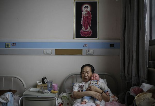 A woman holds a doll donated by a hospice volunteer at Songtang Hospice, Beijing, July 19, 2016.