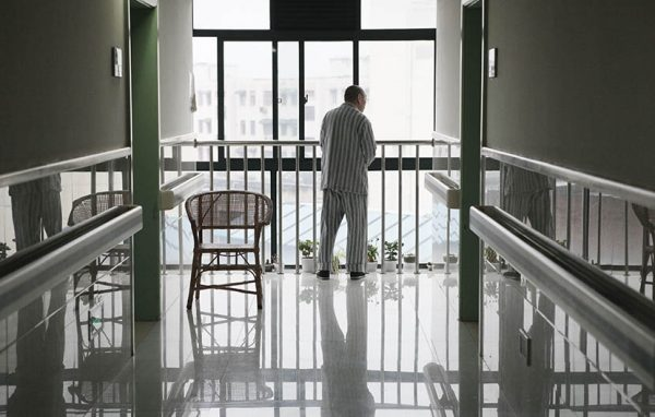 A man stands by a window at the end of the hallway at Putuo District Shiquan Street Community Health Service Center, Shanghai, May 5, 2013.
